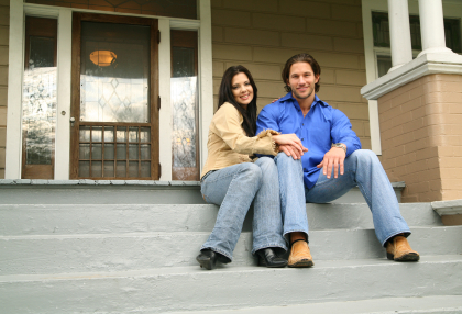 Photo of a young couple with their new house. smiling