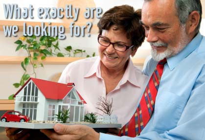 "Photo of a couple looking at a model house with the caption, ""What exactly are we looking for?"""