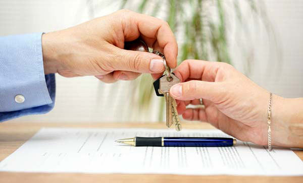 Photo of people exchanging home keys.
