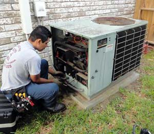 Photo of tech giving an AC a tune-up