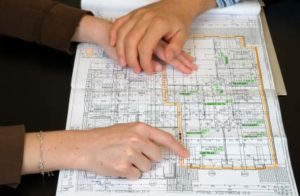 Photo of two people looking at a floorplan - Building a house