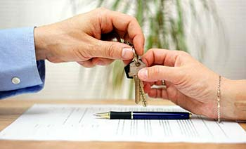Photo of a house seller giving keys to the new home owner - When Is the Best Time to Sell a House?