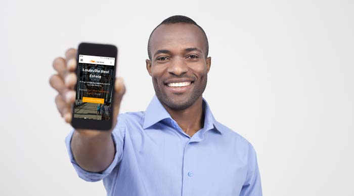 Photo of a man holding up his cellphone - What Every Seller Should Know About Today's Home Buyers