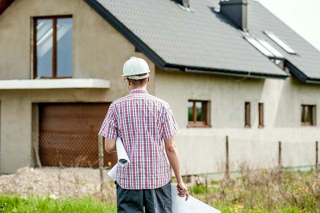 Photo of an architect with house plans looking at home