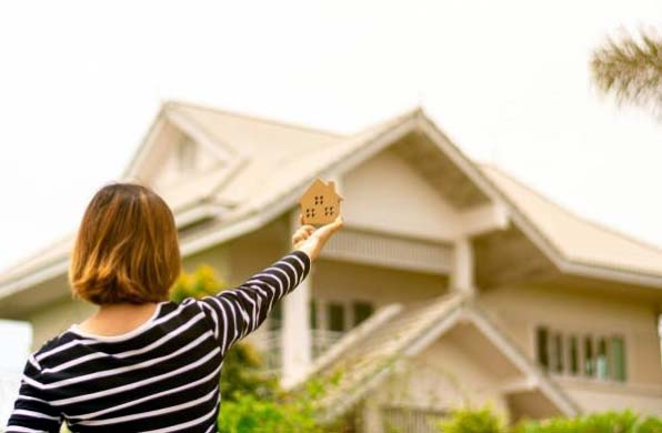 Photo of a woman holding up a block house in front of real house